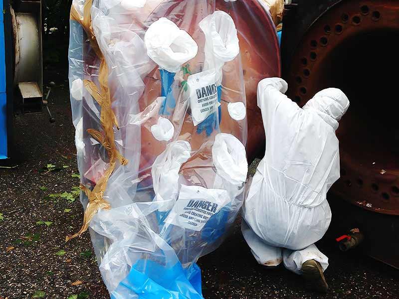 Tecnico in fase di rimozione amianto friabile tramite Glove-bag